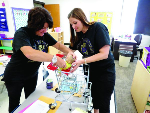 GETTINGREADY — Pre-Kindergarten teacher Natalie Hirkala, right, and autism mentor Wendi Decapio assemble a toy shopping cart on Tuesday in preparation for the Sept. 6 start of Pre-K school in Hancock County. Hirkala, one of two Pre-K teachers at Allison Elementary School, will have 18 students in her classroom. -- Stephen Huba