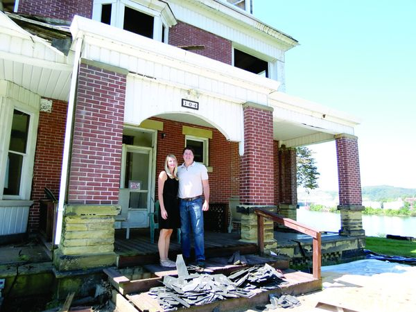 Tommy and Lori Ogden stand on the front porch steps of the old Shrader home, 104 First St., Chester. The slate roof shards are the result of demolition work that started last week and is expected to take three months. -- Stephen Huba