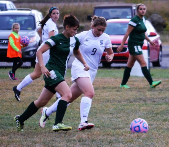MONDAY SOCCER — Madonna's Emma Burns (9) and Brooke's Kaycee Grzybek race for the ball during Monday's match at the J.C. Williams Soccer Complex. The Blue Dons won, 4-1. (Mike Mathison)