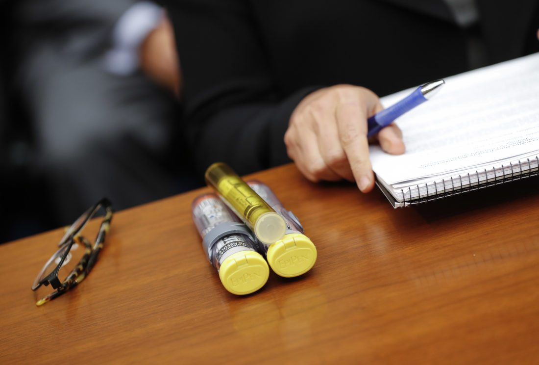 FILE - In this Sept. 21, 2016 file photo, EpiPens brought by Mylan CEO Heather Bresch are seen on Capitol Hill in Washington as she testified before the House Oversight Committee hearing on EpiPen price increases. Senators are asking the Justice Department to investigate whether pharmaceutical company Mylan acted illegally when it classified its life-saving EpiPen as a generic drug and qualified for lower rebate payments to states.  (AP Photo/Pablo Martinez Monsivais, File)