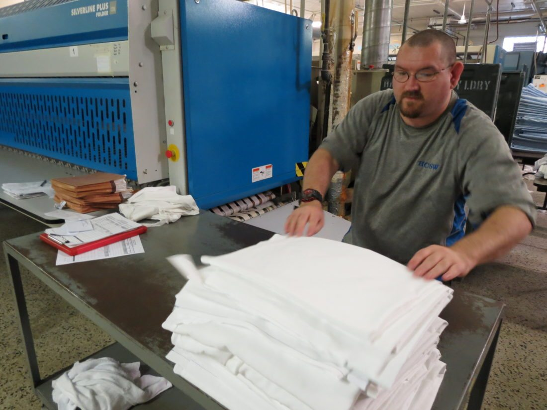 AT WORK — Billy Utt, of New Cumberland, takes sheets off an automated folder and stacks them at the Hancock Laundry, a business of the Hancock County Sheltered Workshop. -- Stephen Huba