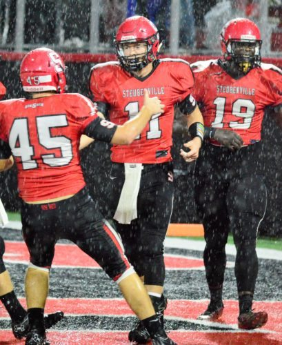 SIX IN THE RAIN — Steubenville's Alec Taylor is congratulated by teammates Charles Reeves (19) and Mitchell Gulan after scoring on a 58-yard pass during the first quarter of Thursday's 47-0 victory over St. Clairsville inside Harding Stadium. (Mike Mathison)