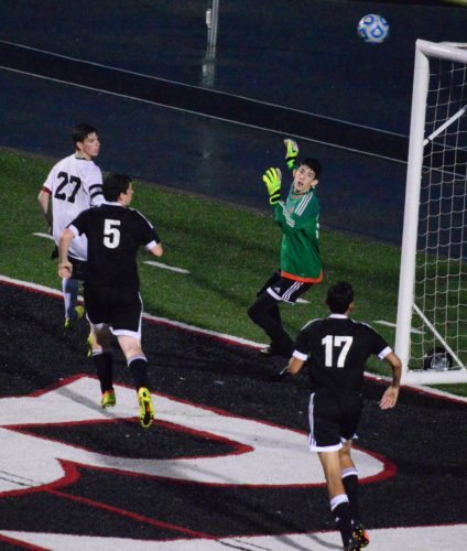 UP, OVER AND GOOD — Weir's Michael Gresko looks back to watch his header slip into the net over Trinity Christian gioalie Fletcher Harstock for the first goal in Thursday's 5-1 win over the Warriors in the West Virginia Class AA-A sectional semifinal at Jimmy Carey Stadium. The Red Riders will next play Saturday at 5 p.m. at Brooke. (Mike Mathison)