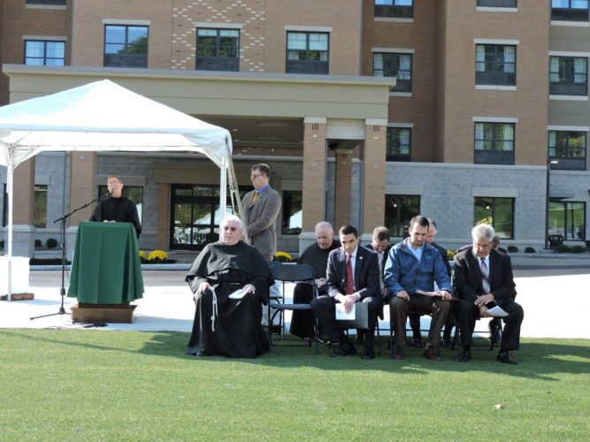 GRAND OPENING — The Rev. Nathan Malavolti, vice president of pastoral care and evangelization, delivered the opening prayer at grand opening ceremonies Thursday at the Inn of Franciscan Square on University Boulevard. Seated in front of the new hotel were several local and state officials along with representatives of Franciscan University of Steubenville. -- Dave Gossett