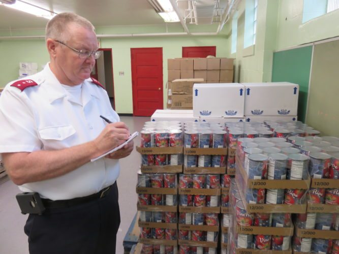 LOOKINGFORHELP — Capt. Steve Griffin, commanding officer of the Salvation Army of Steubenville, checks out the status of canned goods in stock for distribution to the needy this Christmas. The busy holiday season is approaching with applications to receive food and toys being taken beginning Monday. -- Janice Kiaski