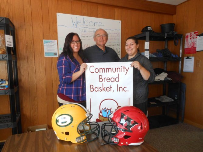 RIVALS — Volunteers, from left, Kayla Chappell, Jim Pauchnick and Jena Lindsey will be collecting food for the Community Bread Basket at the Weir High School-Brooke High School football game Friday at Brooke Memorial Stadium on Bruin Drive. -- Contributed