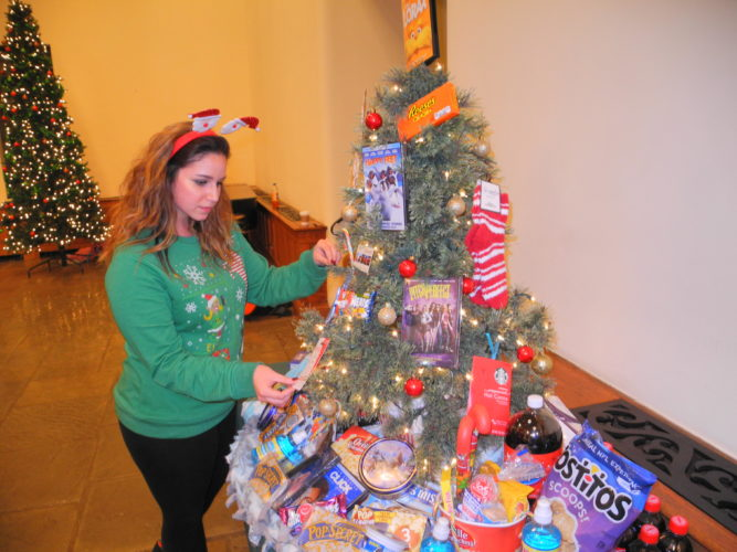 A MOVIE LOVER'S TREE — Kristen Ewing of the Phi Mu sorority at Bethany College inspects the movie lover's tree sponsored by the group for an auction Thursday at Bethany College. The tree was one of nearly two dozen of various sizes and themes that went on the auction block to raise funds for Bernie's Kids, a local toy drive for Brooke County children in need. -- Warren Scott