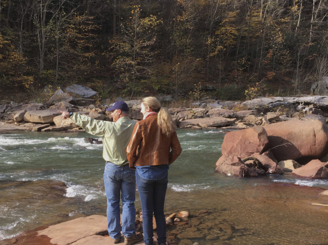 In this Nov. 1, 2016 photo, Keith Fisher of the Nature Conservancy shows colleague Abigail Strassman the start of the Cheat River Canyon near Albright, West Virginia. The conservancy and other environmentalists joined with the state to buy the canyon and its eight-mile stretch of the once badly polluted river. (AP Photo/Michael Virtanen)
