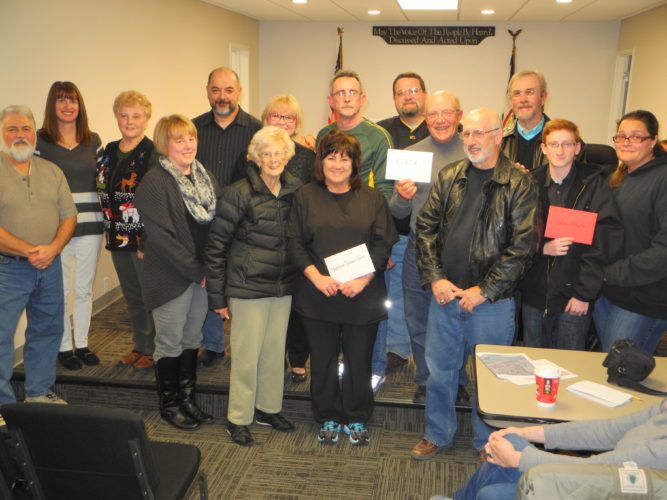 CHRISTMAS SPIRIT — The Follansbee Christmas in the Park Committee passed out checks of $2,400 each to the Anderson Children's Home, the R.E.A.C.H. Program and Andrew Scheetz, a boy with diabetes, at Monday's Follansbee Council meeting. On hand were, from left, front, committee members Tom DiBattista, Stacy Williams and Nina Meca, Eberle Lazear of the Anderson Children's Home, Charles Sargent of the R.E.A.C.H. Program and Scheetz and his mother, Barbara, and back, committee members Dana Griffin, Betty Shaffer, Bill Secrist and Kathy Santoro, Josh Swartz of Anderson's Children's Home and John Casinelli, Ed Wilkerson and Rob Carpenter of the R.E.A.C.H. Program. -- Warren Scott