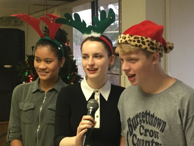 "SOCIAL HELD — Burgettstown High School student Emma Gragan, center,, organized and executed the ""Coraopolis Christmas Social 2016"" recently, where she has been holding the event since she was 10 years old. She was joined in holding a carol sing-along by fellow Burgettstown High students Tisha Moss, left, and Jim Gallucci, right, and the young people also served coffee and cake during an intermission. -- Contributed"