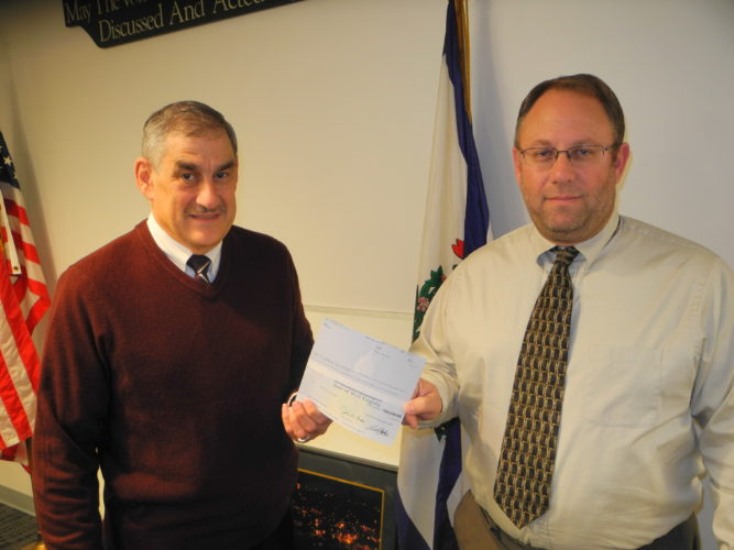 UNCLAIMED FUNDS DELIVERED — Follansbee City Manager John DeStefano, left, was presented a check for $10,497 in unclaimed funds belonging to the city, from Tim Hooper, local government specialist for West Virginia State Treasurer John Perdue.  -- Warren Scott