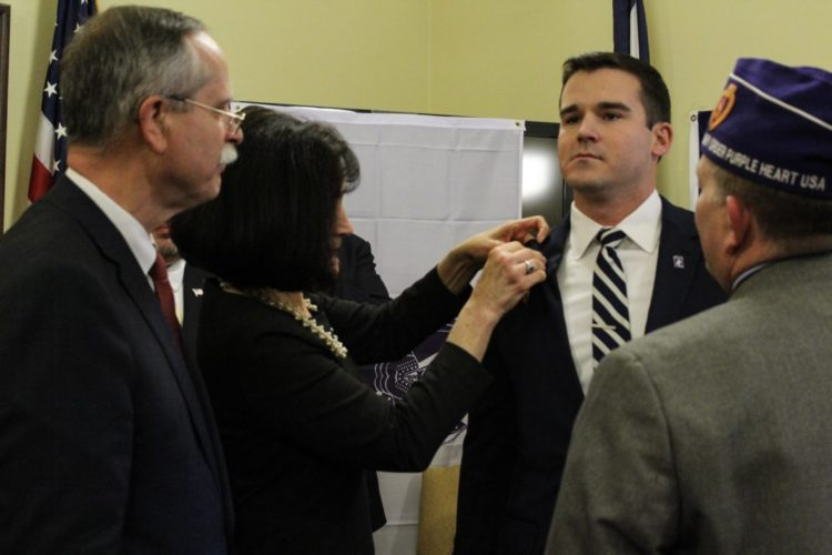 SPECIAL MOMENT — Debbie Warner, wife of West Virginia Secretary of State Mac Warner, pins the Purple Heart award on her son, retired U.S. Army Capt. Steven Warner, Monday in Charleston. Looking on is U.S. Rep. David McKinley, R-W.Va. -- Contributed