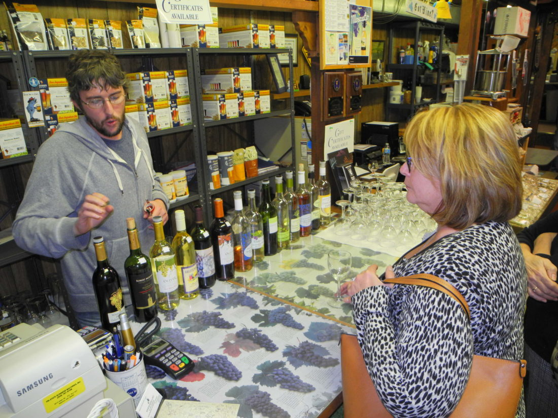 GETTING A SAMPLE — Derek Sliday, owner of The Winemaker's Loft and Gift Shoppe in Follansbee, offered samples of wine and appetizers to visiting members of the Brooke County Economic Development Authority and guests, including Jacie Ridgely of the Wellsburg Chamber of Commerce, Wednesday. -- Warren Scott