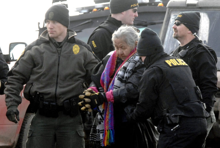 PROTEST —An elderly woman is escorted to a transport van after being arrested by law enforcement at the Oceti Sakowin camp as part of the final sweep of the Dakota Access pipeline protesters in Morton County, Thursday, near Cannon Ball, N.D. -- Associated Press