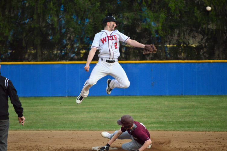 Mike Mathison FLYING HIGH —  Weir High shortstop Jacob Rosnick is in the air as he watches the ball go into center field as Wheeling Central's Pat Brown steals second base. The Red Riders are 2-0 on the young season after the 5-3 victory Friday at Bowman Field.
