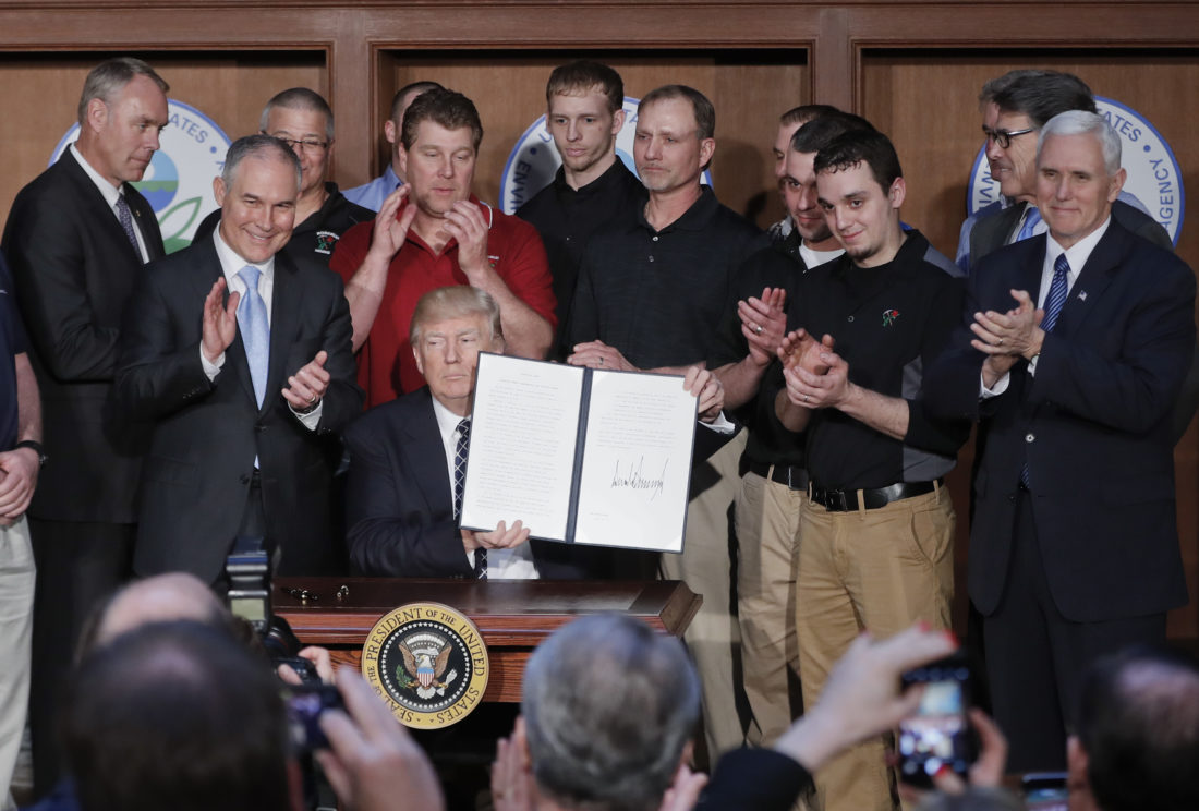 MINERS' HOPES — President Donald Trump, accompanied by coal miners and Interior Secretary Ryan Zinke, left, Environmental Protection Agency Administrator Scott Pruitt, second from left, Energy Secretary Rick Perry, second from right, and Vice President Mike Pence, right, holds up the signed Energy Independence Executive Order, Tuesday, at EPA headquarters in Washington. -- Associated Press